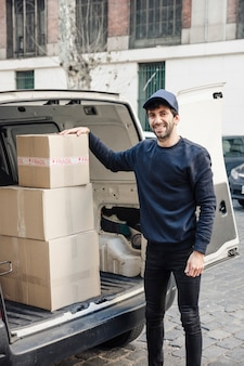 Portret van een gelukkige leveringsmens die zich dichtbij voertuig met kartondozen bevindt