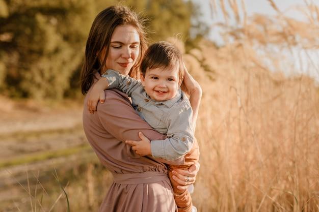 Portret van een gelukkige liefhebbende moeder die haar zoontje knuffelt in het zonnige park in de buurt van de rivier.