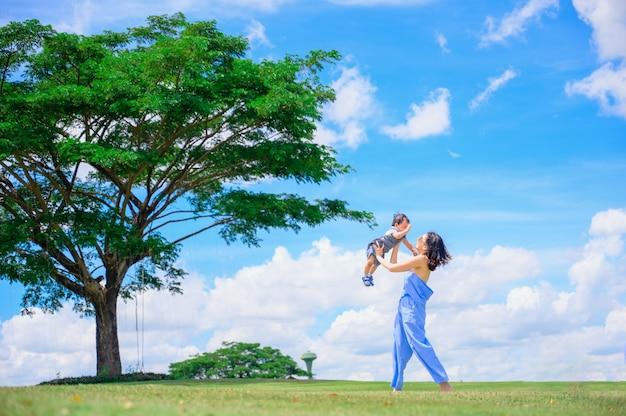 Portret van een gelukkige liefhebbende moeder en haar baby buitenshuis