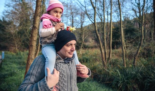 Portret van een gelukkige man die een ritje op de rug geeft aan een klein meisje in het bos