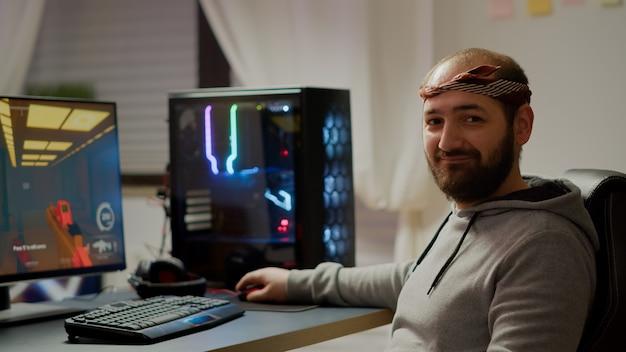 Portret van een gelukkige man die naar een camera kijkt die lacht en een online fps-shooter-videogame speelt voor een virtueel toernooi. cyber presteert op krachtige computer met rgb-trefwoord tijdens kampioenschap thuis