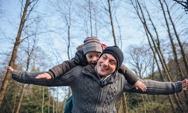 Portret van een gelukkige man die op de rug ritje geeft aan een lachend kind en zijn armen in het bos steekt