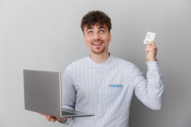 Portret van een gelukkige man gekleed in een shirt glimlachend terwijl hij een zilveren laptop en creditcard vasthoudt die over een grijze muur is geïsoleerd
