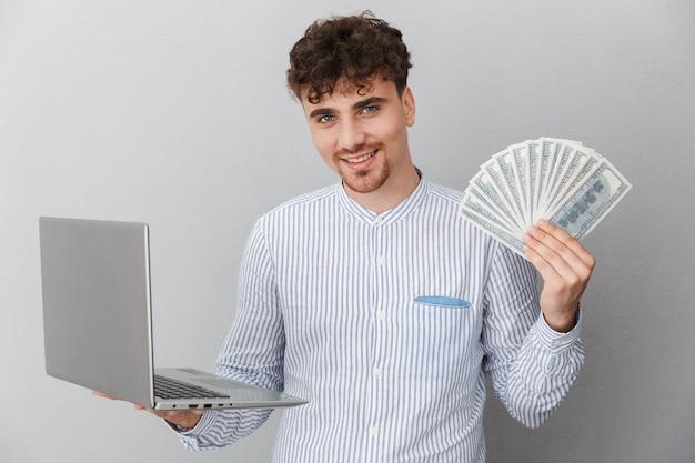 Portret van een gelukkige man gekleed in een shirt glimlachend terwijl hij een zilveren laptop vasthoudt en een hoop geld cash geïsoleerd over een grijze muur