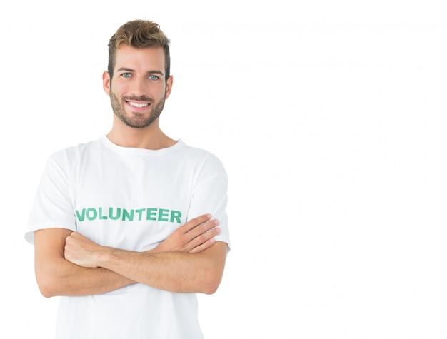 Portret van een gelukkige mannelijke vrijwilliger die zich met gekruiste handen bevindt