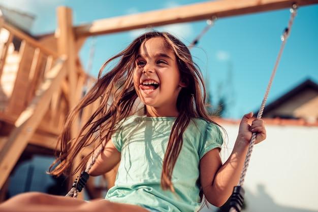 Portret van een gelukkige meisjezitting op een schommeling en het glimlachen