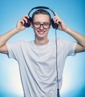 Portret van een gelukkige mens die de muziek in hoofdtelefoons luistert en hen van hoofd over blauwe achtergrond verwijdert.