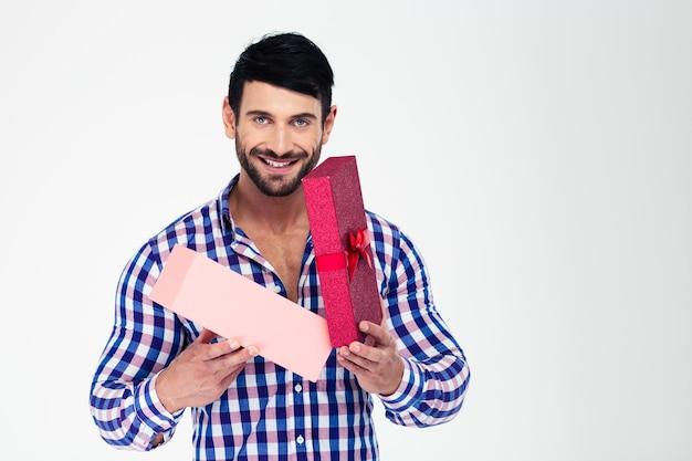 Portret van een gelukkige mens die giftdoos opent die op een witte muur wordt geïsoleerd