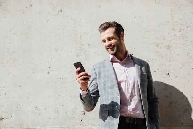 Portret van een gelukkige mens die in jasje mobiele telefoon houdt