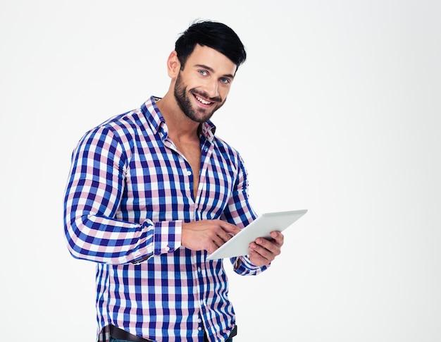 Portret van een gelukkige mens die tabletcomputer met behulp van die op een witte muur wordt geïsoleerd en voorzijde bekijkt