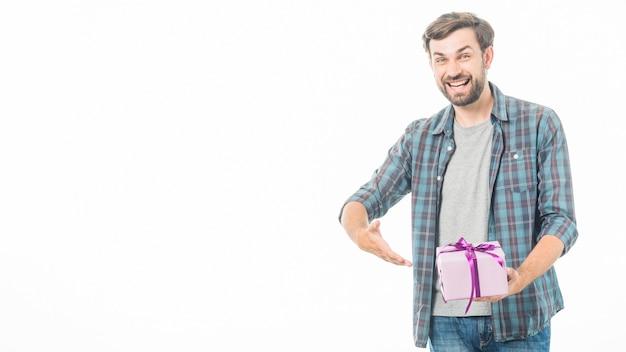 Portret van een gelukkige mens die verjaardagsgift op witte achtergrond toont