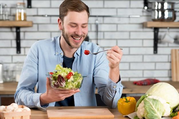 Portret van een gelukkige mens die verse salade in de keuken eet