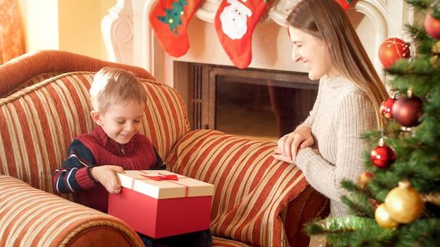 Portret van een gelukkige moeder die een kerstcadeau in een mooie doos geeft aan haar zoontje dat in een fauteuil naast een prachtige kerstboom zit. perfect beeld voor wintervakanties en vieringen