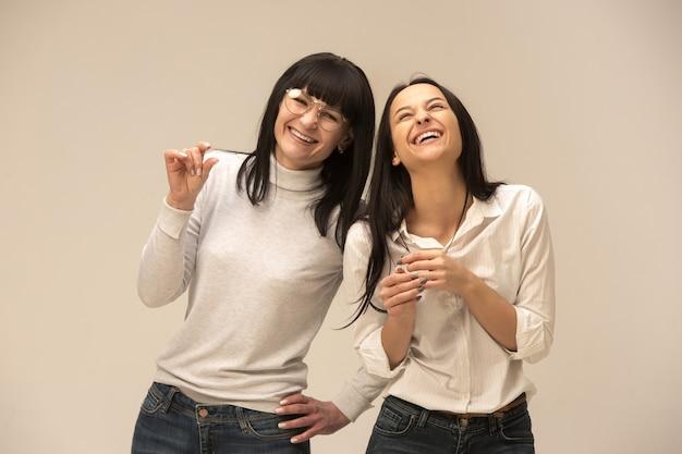 Portret van een gelukkige moeder en dochter in de studio op een grijze achtergrond. menselijke positieve emoties en gezichtsuitdrukkingen concept