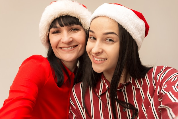 Portret van een gelukkige moeder en dochter in kerstmanhoed op grijs