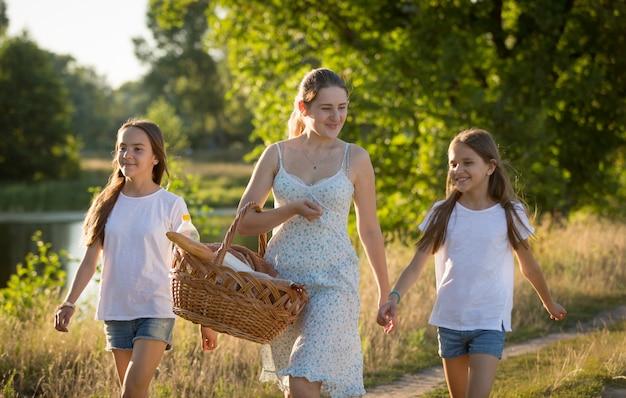 Portret van een gelukkige moeder met twee dochters die bij zonsondergang langs de rivier in de weide lopen
