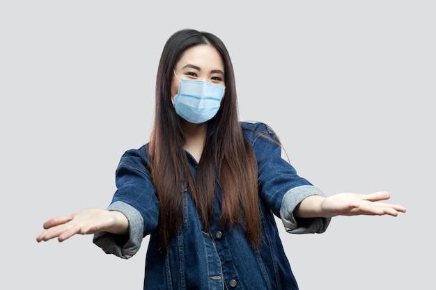 Portret van een gelukkige mooie brunette aziatische jonge vrouw met een medisch masker in een blauwe jas die naar de camera kijkt met opgeheven armen om te delen en te glimlachen. studio opname, geïsoleerd op een grijze achtergrond.