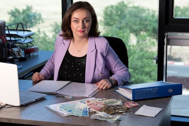 Portret van een gelukkige mooie brunette die aan haar bureau werkt met documenten, laptop, dollars, britse ponden, nieuwe sikkels-bankbiljetten en -munten. zakenvrouw bezig met papierwerk.