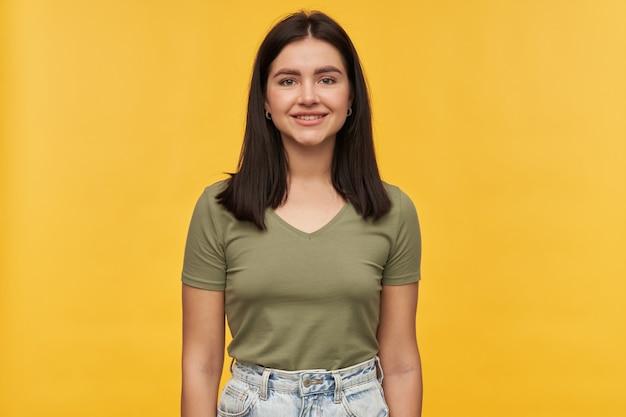 Portret van een gelukkige mooie donkerbruine jonge vrouw in vrijetijdskleding die over gele muur staat en glimlacht