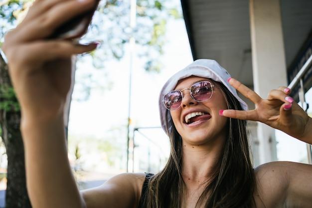 Portret van een gelukkige, mooie en jonge vrouw die een foto van zichzelf neemt en het teken van overwinning toont