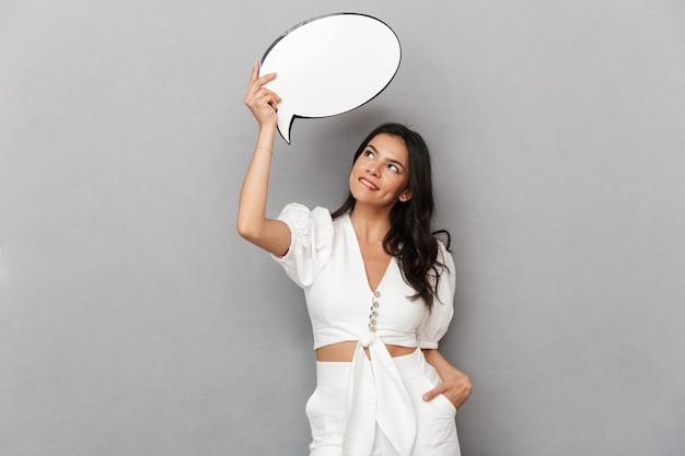 Portret van een gelukkige, mooie jonge brunette vrouw met een zomeroutfit die geïsoleerd staat over een grijze muur en een lege tekstballon vasthoudt