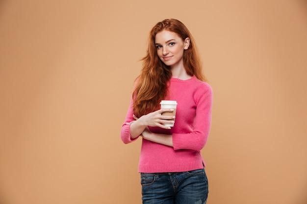 Portret van een gelukkige mooie kop van de de holdingskoffie van het roodharigemeisje