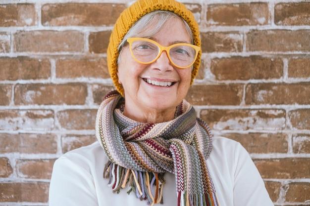 Portret van een gelukkige, mooie oudere vrouw met een wintermuts en sjaal - bakstenen muurachtergrond