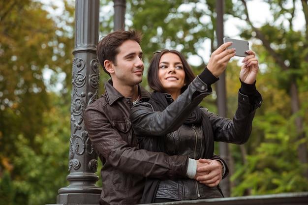 Portret van een gelukkige mooie paar selfie foto maken op smartphone buitenshuis