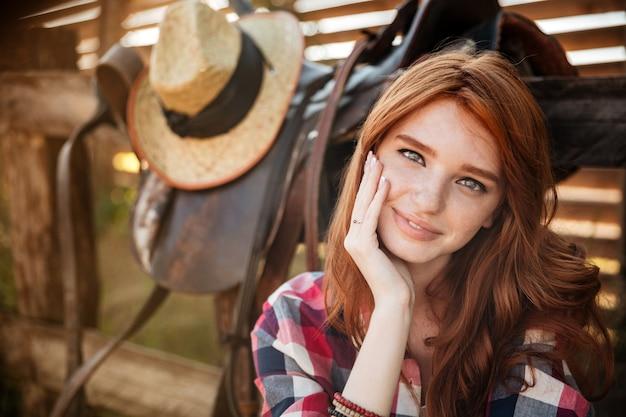 Portret van een gelukkige mooie roodharige veedrijfster die bij de boerderijomheining rust close-up