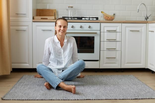 Portret van een gelukkige mooie vrouw die binnen poseert, naar de camera kijkt terwijl ze thuis op de keukenvloer zit, een meisje met een paardenstaart die een spijkerbroek en een wit overhemd draagt.