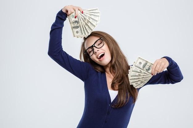 Portret van een gelukkige mooie vrouw die met gesloten ogen geld houdt dat op een witte achtergrond wordt geïsoleerd