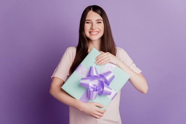 Portret van een gelukkige mooie vrouw houdt het cadeau vast op de paarse muur