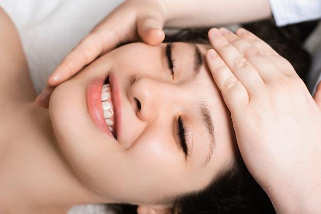 Portret van een gelukkige mooie vrouw lachend met gesloten ogen close-up terwijl het hebben van gezichtsprocedures in een wellness-kuuroord.