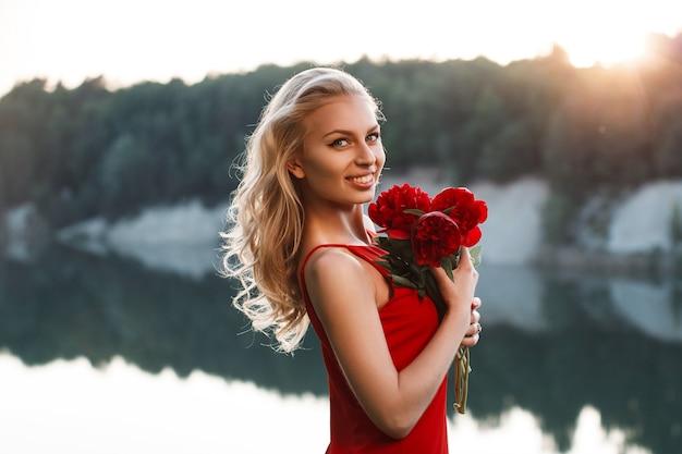 Portret van een gelukkige mooie vrouw met een boeket van pioenroos