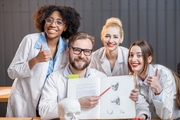Portret van een gelukkige multi-etnische groep medische wetenschappers of studenten die samen met een boek op kantoor of in de klas zitten