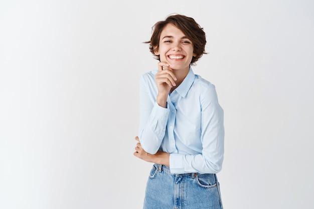 Portret van een gelukkige openhartige vrouw die lacht, er vrolijk en opgewekt uitziet, het gezicht aanraakt zonder make-up, op een witte muur staat