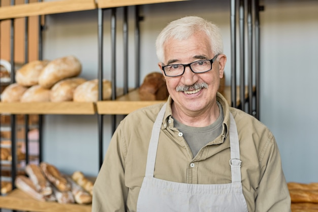 Portret van een gelukkige oude bakker in een bril en een schort die tegen de kraam staat met brood in de winkel