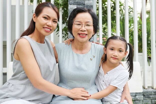 Portret van een gelukkige oudere vrouw die graag tijd doorbrengt met dochter en kleindochter die haar thuis bezoeken op verjaardag