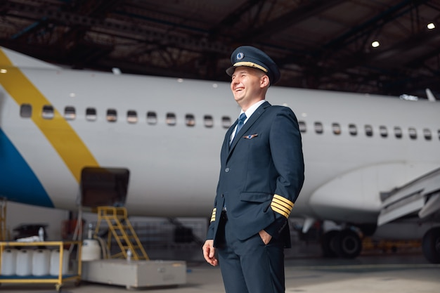 Portret van een gelukkige piloot in uniform die wegkijkt, klaar voor de vlucht, staande voor een groot passagiersvliegtuig in de luchthavenhangar. vliegtuigen, beroep, transportconcept