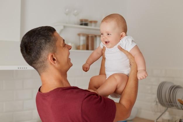 Portret van een gelukkige positieve vader die een charmant babymeisje vasthoudt met een wit t-shirt in handen, opgewonden kind houdt van tijd doorbrengen met papa, familie poseren in lichte kamer.