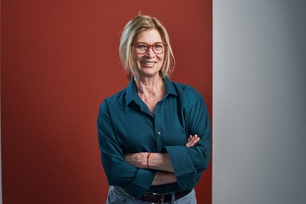 Portret van een gelukkige rijpe vrouw in een bril die naar de camera glimlacht terwijl ze staat met de armen gekruist tegen de rode achtergrond