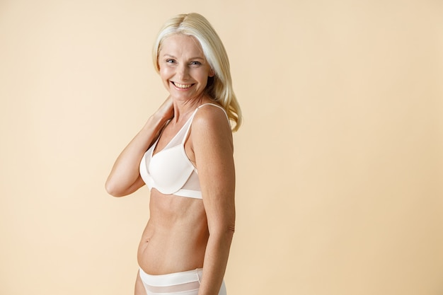 Portret van een gelukkige rijpe vrouw met blond haar in wit ondergoed glimlachend naar de camera poseren