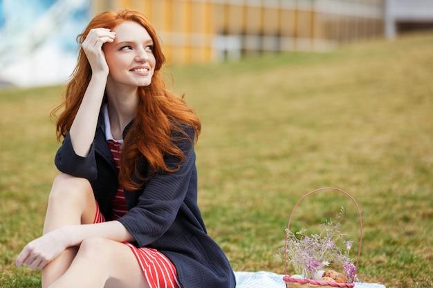 Portret van een gelukkige rode hoofdvrouw die picknick heeft