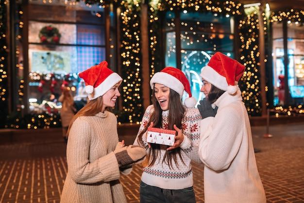 Portret van een gelukkige, schattige jonge groep vrienden die elkaar knuffelen en glimlachen tijdens het wandelen op kerstavond buitenshuis, met kerstmutsen, veel lichten op de achtergrond