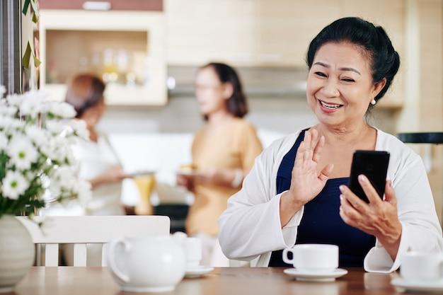 Portret van een gelukkige senior vietnamese vrouw die met de hand zwaait wanneer ze haar vrienden of familieleden video belt