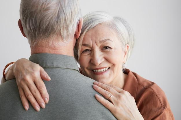 Portret van een gelukkige senior vrouw die haar echtgenoot omhelst en naar de camera kijkt tegen een witte achtergrond