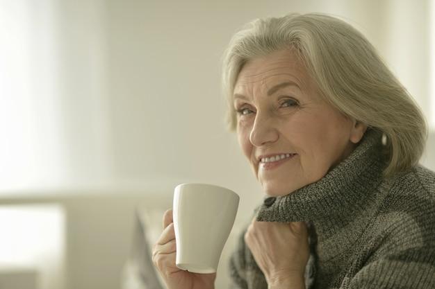 Portret van een gelukkige senior vrouw met cup