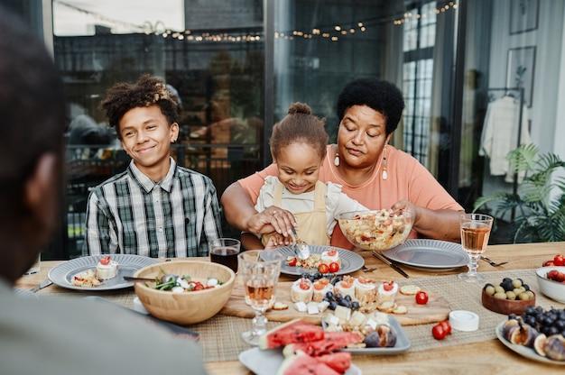 Portret van een gelukkige senior vrouw met kleinkinderen die samen genieten van een familiediner
