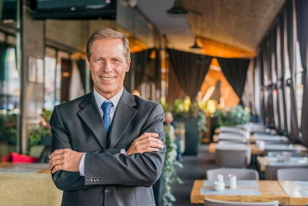 Portret van een gelukkige succesvolle zakenman die zich in restaurant met gekruist wapen bevindt