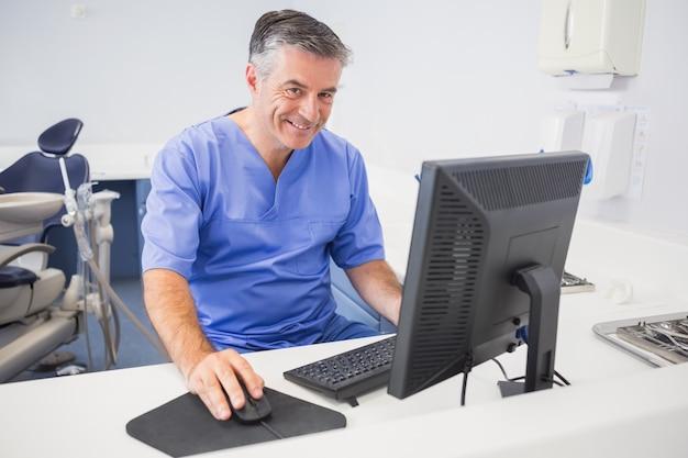 Portret van een gelukkige tandarts die computer met behulp van